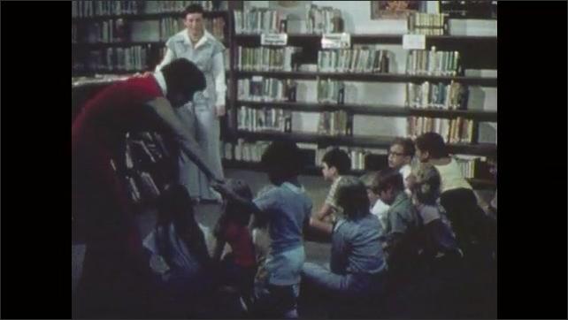 1970s: Woman seats children on floor. Woman speaks to kids