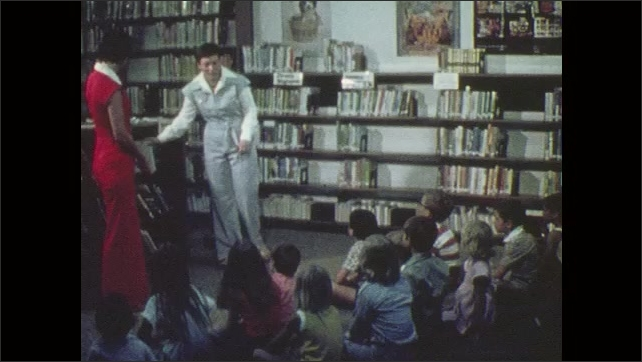 1970s: Woman talks and points. Woman opens book. Children sit on floor