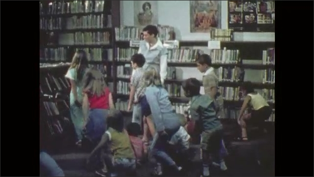 1970s: Woman speaks to children. Children stand and disperse