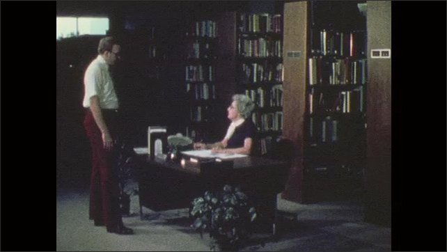 1970s: Man speaks to woman in library