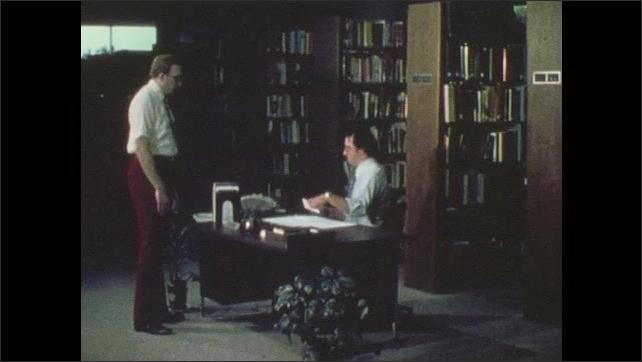 1970s: Men speak in library. Man writes