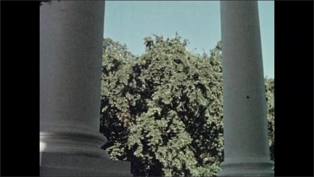 1950s: american elm grows on lawn near two tall columns of North portico of White House as cars and trucks drive on Pennsylvania Avenue.