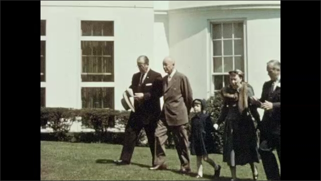 1950s: president Dwight Eisenhower walks from White House onto South Lawn with secretary of agriculture Ezra Benson, men in suits, woman and girl in a hat and coat.