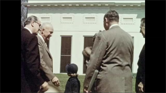 1950s: secretary of agriculture Ezra Benson holds branch of tree. president Dwight Eisenhower shakes hands with first wife mamie, granddaughter Susan and men in suits near White House on South Lawn.
