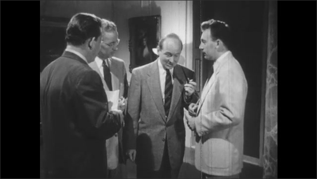 1950s: Men ask questions with notepads to Secretary of State who answers, smokes pipe, dismisses himself.