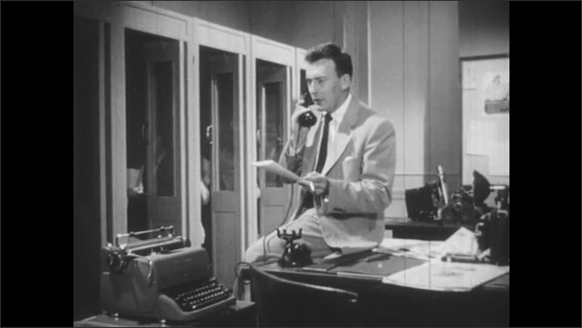 1950s: Man sits on office desk with paper, speaks on phone, man passes with paper one way and then another.