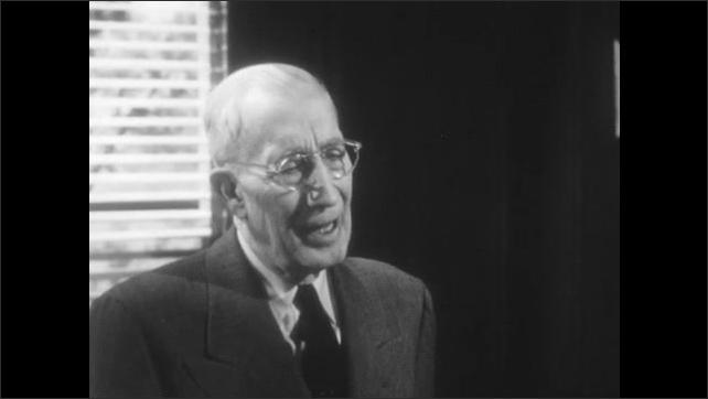 1950s: Young man speaks. Elderly man responds. Men stand around desk and talk.