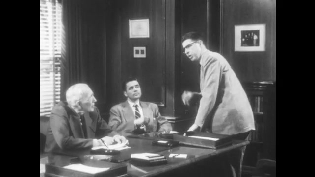 1950s: Man hands letters to elderly man. Men sit at desk and talk. Man stands from desk and sits on edge of table. Man speaks passionately to men at desk.