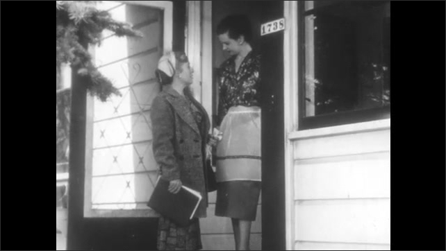 1950s: Woman answers front door. Women stand at front door and talk. Women enter home and shut screen door.