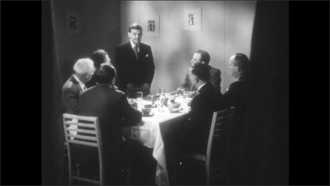 1950s: Group of men sit around table, talk.