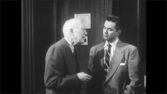 1950s: Two men stand in office, older man talks to younger man.