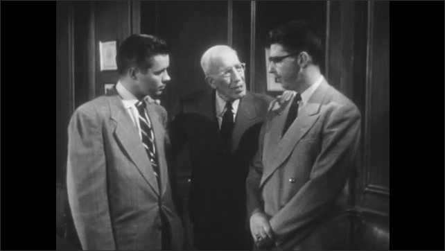 1950s: Three men stand in office, have conversation. Younger men walk away.