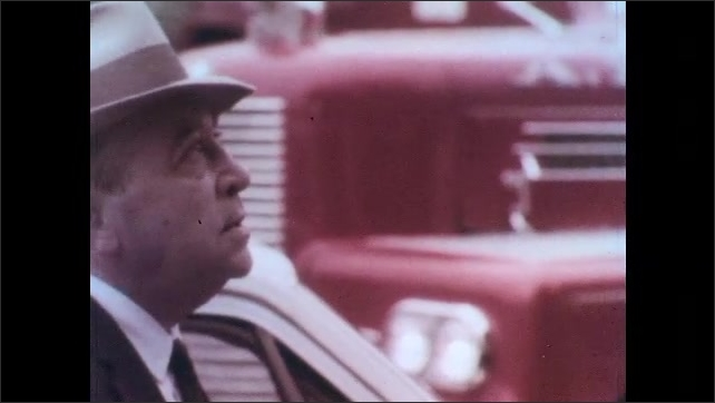 1970s: UNITED STATES: man in street. Mayor examines damage in city. Man speaks to emergency worker. Policeman holds back people. Family search for dead in rubble