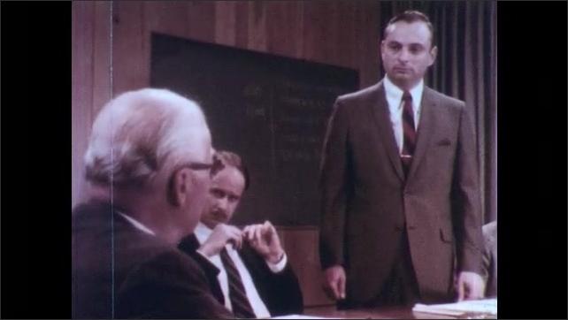 1970s: UNITED STATES: man addresses people in meeting. Meeting members listen to man speak. Man speaks at meeting.