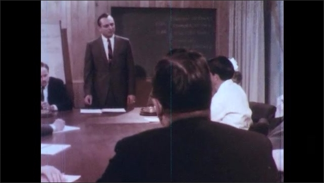 1970s: UNITED STATES: man stands in front of people at meeting. Members sit in board meeting.