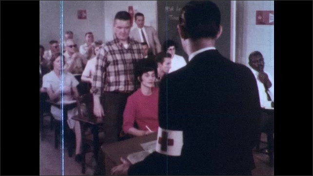 1970s: Man with red cross armband speaks to class of hospital workers, such as maintenance.