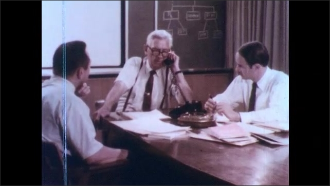 1970s: Public health officer talks on telephone in meeting room.