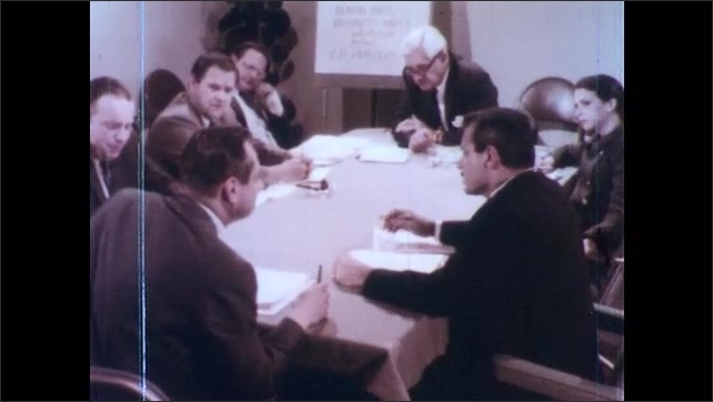 1970s: Men and one woman plan around conference table, discussing their plans animatedly.