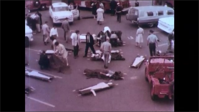 1970s: Pretend victims lay on gurneys in a parking lot. First responders come to assess the situation with emergency vehicles in the background.