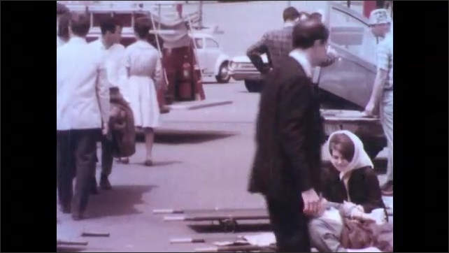 1970s: Pretend victims are lifted on stretchers on to ambulances. First responders assess the scene and injured people.