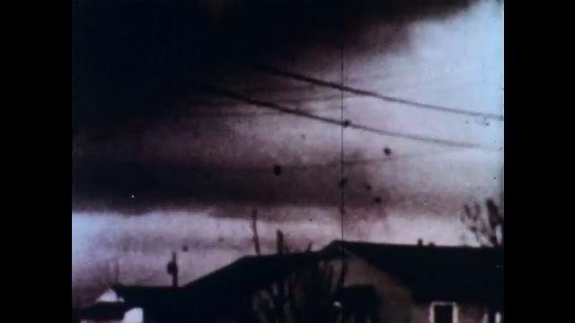 1970s: UNITED STATES: debris from tornado. Funnel of tornado. Tornado sweeps through town