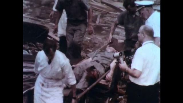 1970s: UNITED STATES: injured man on stretcher. Ladies hug by rubble. Victims of explosion. Family search for casualties
