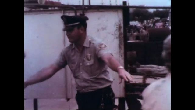 1970s: UNITED STATES: officer directs people at explosion sight. Man with blood on arm. Medic treats casualty at scene of explosion.