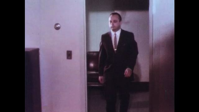 1970s: UNITED STATES: man walks into room. Man speaks on telephone. Man speaks to lady in hospital management room.