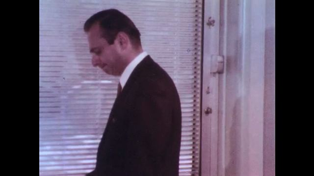 1970s: UNITED STATES: man looks through blinds at window. Man speaks on phone. Lady writes notes.