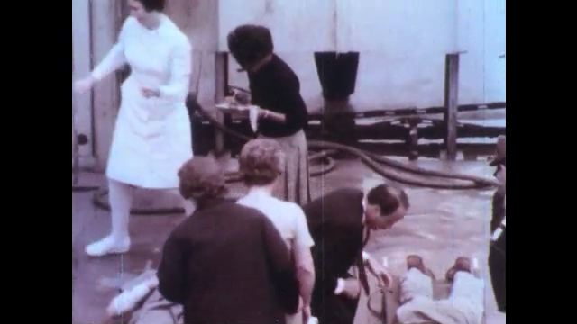 1970s: UNITED STATES: casualties at site of explosion. Plant workers at sight. Patient on stretcher.