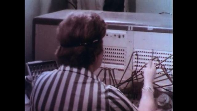 1970s: Switchboard operators connect emergency calls. Men in suits check their watches and discuss planning. Watch reads 11:04. Emergency vehicles race down the street.