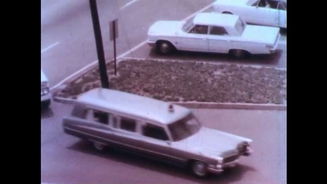 1970s: Ambulance and civil defense vehicles race down empty streets. Pretend victims lay on gurneys in a parking lot. First responders come to assess the situation.