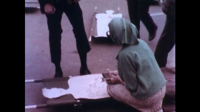 1970s: Woman assesses paper patient on stretcher. Man helps her assess the injuries. Woman makes notes. Emergency vehicles and responders on test.
