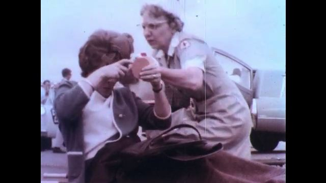 1970s: Nurse reapplies bloodied bandage and pretend patient is frustrated about her hairdo. Pretend patient lies down on stretcher and folds her arm crossly. Nurse pats her arm.