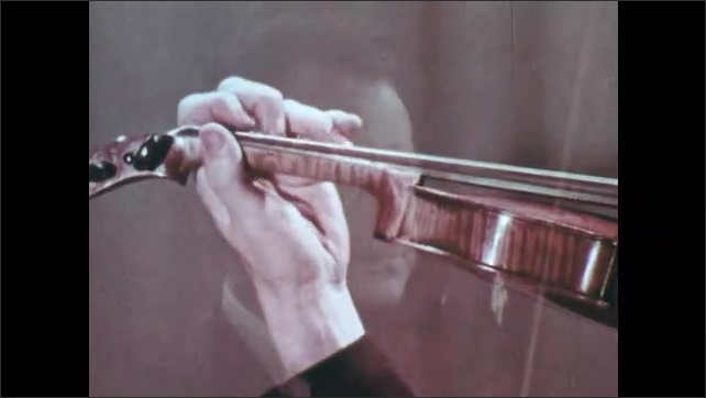 """1970s: Hand with suited arm plays violin. Words on screen: """"Left hand elevation."""" Face of man playing violin. His name is posted on the screen."""