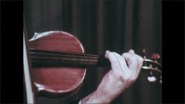 1970s: Hand with suited arm plays violin and shakes with vibrato. Different view of hand. Man plays violin.