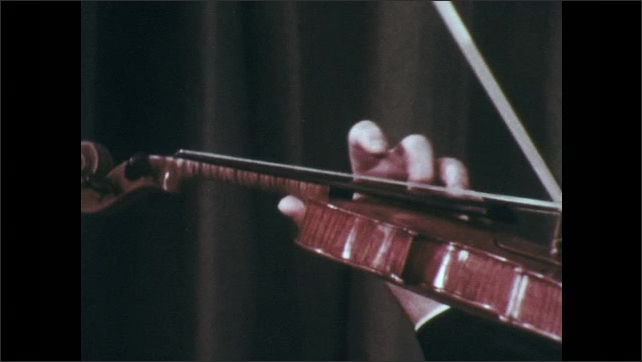 1970s: Hand with suited arm plays violin and shakes with vibrato.