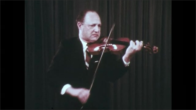 1970s: Older man with suit plays violin in room with curtained background.