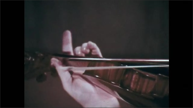 1970s: Older man with suit plays violin in room with curtained background. Hands with suited arm play violin.