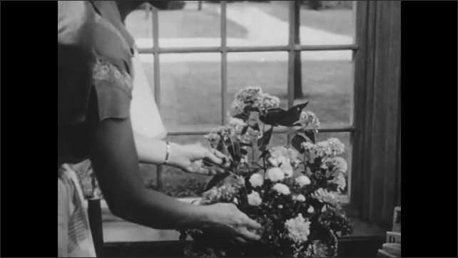 1940s: Telephone sits on sofa end table. Woman sits vase of flowers on table near picture window. Pedestrians and traffic on city street.