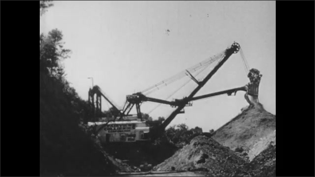 1940s: Crane dumps soil on large pile. Water wheel spins outside of wooden mill building.
