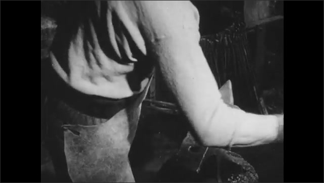 1940s: Blacksmith pounds hot horseshoe with hammer in workshop. Man shaves barrel stave with hand lathe.