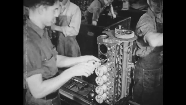 1940s: Man removes engine casing from industrial drill. Men operate machines on assembly line. Man inserts pistons into car engine. Men position car frame onto assembly line. Wheel spins.