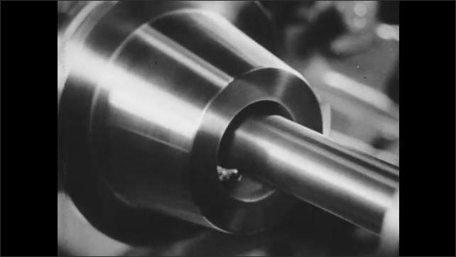 1940s: Machine blade carves metal from part. Hand removes auto parts from fabrication machine. Men operate machining tools to shape metal parts. Printing press drum rolls.