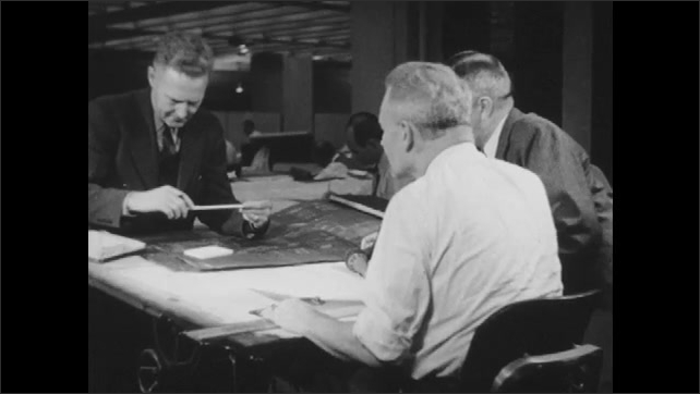 1940s: Men talk at desk in office. Man observes tubes in lab. Engineers consult blueprints. Man shows sales chart to men in office.
