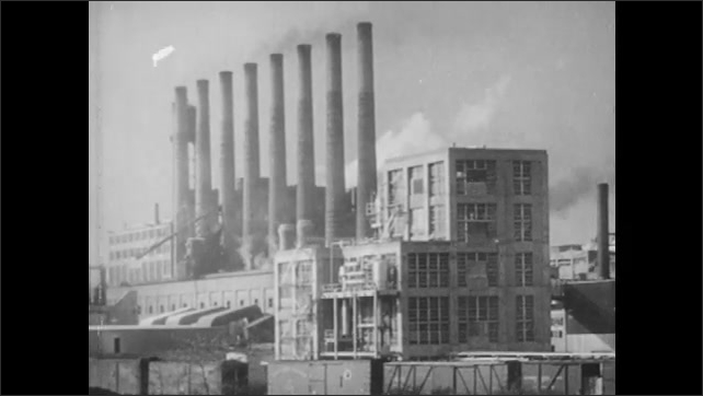 1940s: Workers enter plant and punch timecards. Smoke billows from factory building. Illustrated picture of city and industrial buildings.