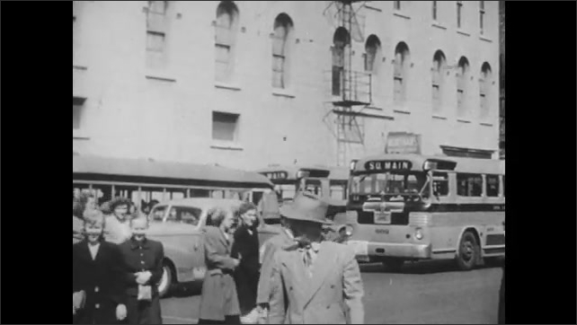 1940s: Man drives train. Pedestrians and traffic move through busy city streets.