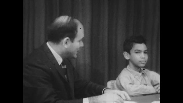 1960s: Man sits at table with kids, talks. Kids state their names.
