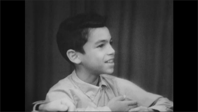 1960s: Little boy sits at table, talks and laughs.