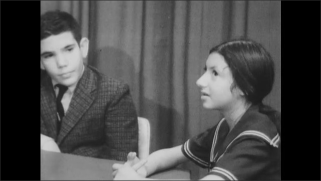 1960s: Boy and girl sit at table, girl talks.